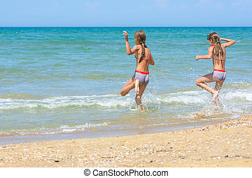 Two sisters run into the sea on a hot sunny day