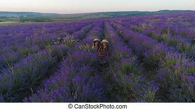 Two sisters sit in lavender and eat apricots in slow motion...