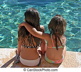 sisters - two sisters sitting at pool side with arm over one...
