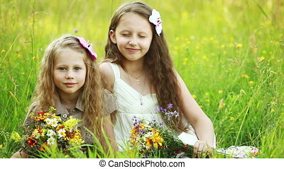 Two sisters sitting on the grass