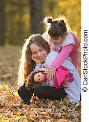 Two sisters sitting on the ground in autumn park - a little one holding a doll