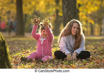 Two sisters sitting on the ground in autumn park