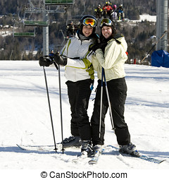 Two sisters skiing together on mountain slopes