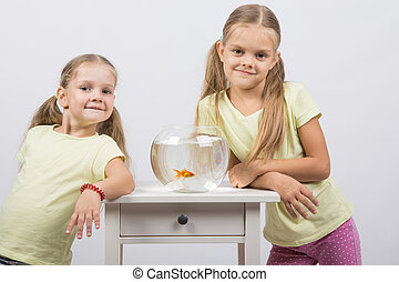 Two sisters stand at the small fishbowl with goldfish