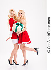 Two sisters twins in santa claus dresses holding one present