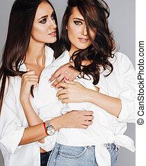 two sisters twins posing, making photo selfie, dressed same...