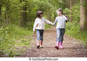 Two sisters walking on path holding hands smiling