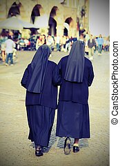 sisters with black dresses and a veil