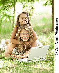 Two sisters with laptop in the park.
