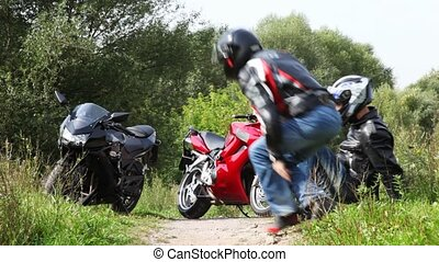 Two sits on grass, then sit down on motorcycles and leave