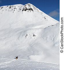 Two skiers and snowy off-piste slope with traces of skis, snowboards and avalanches.