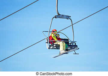 Two skiers lifting on chairlift against blue sky