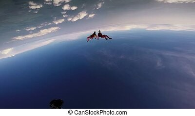 Two skydivers dancing together in cloudy sky. Sunny day....