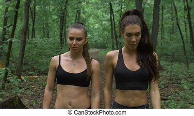 Two slender girl walking through the forest after training and talking. They communicate with each other on various topics and smile.
