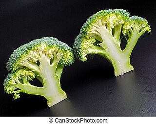 two sliced broccoli sprigs on a black background close up