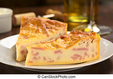 Two slices of cheese and ham quiche with white wine in the...