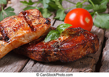 two slices of juicy grilled meat with basil and tomatoes on...