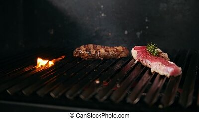 Two slices of meat of varying degrees of readiness lie on the grill, cooking and Haute cuisine concept