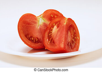 Two slices of red tomatoes on a white plate