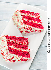 Two slices of red velvet cake on the white plate