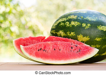 Two slices of ripe red juicy watermelon on a wooden table in the garden in summer time
