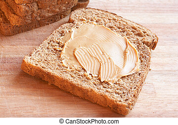 Two slices of Tasty healthy wholewheat bread with peanut butter spread on the table