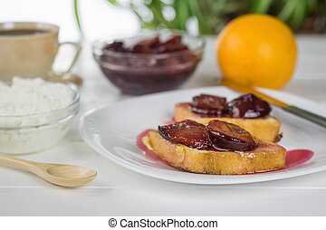 Two slices of toasted French bread smeared with plum jam on ...