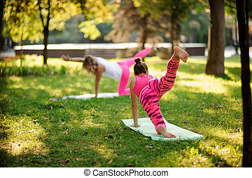 Two slim women doing yoga exercises on the grass in a park