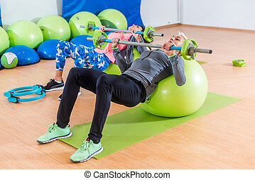 Two slim women exercising with barbell and Swiss ball in...