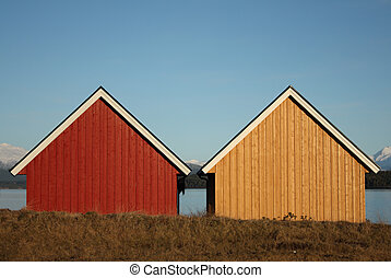 Two small almost identical houses by the sea, one yellow and one red.