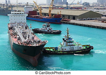 Two small boats docked to industrial ship in port at sunny...