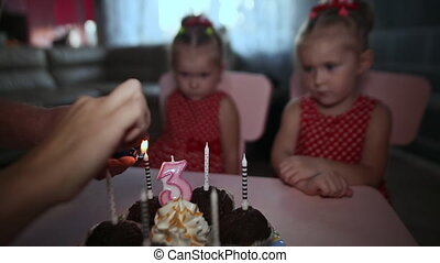 Two small charming and dressed twin sisters gathered near the festive cake with burning candles. Birthday in the family.