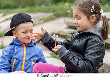 Two small children are playing with dandelions on a walk.