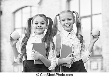 two small girls ready to study. do homework together. sisters at lunch break with apple. healthy and happy childhood. sisterhood and friendship. best friends from school. Pleasant timespending