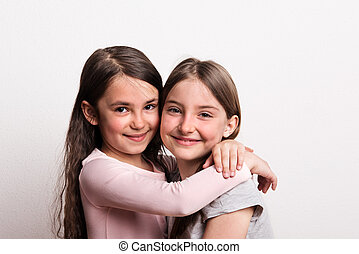 Two small girls standing in a studio., hugging.