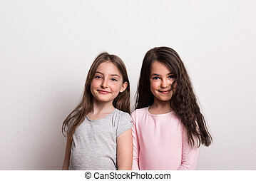 Two small girls standing in a studio.