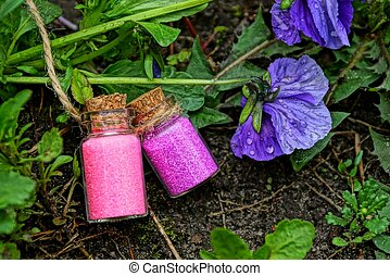 two small glass bottles with red sand among herbal plants and lilac flowers