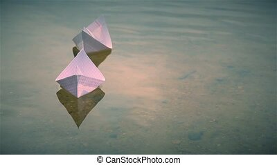 Two small paper boats floating on the lake
