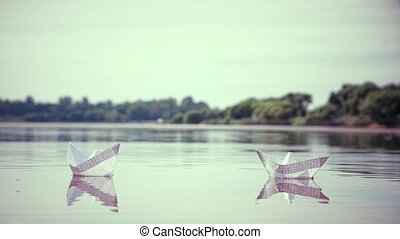Two small paper boats floating on the water