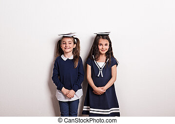 Two small schoolgirls with uniform standing in a studio, notepads on their heads.