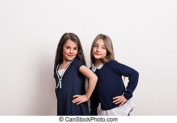 Two small schoolgirls with uniform standing in a studio.