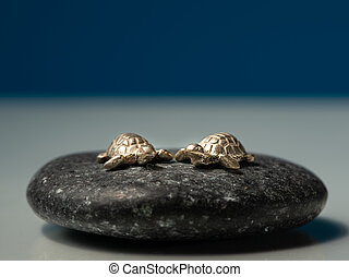 Two small sea turtles made of gold sitting on a black stone