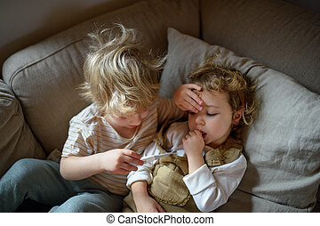 Two small sick children brother and sister at home lying in bed.