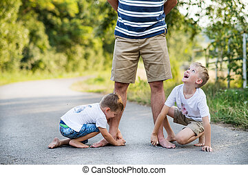Two small sons playing with father on a road in park on a summer day.