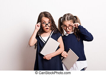 Two small surprised schoolgirls with glasses and open mouth standing in a studio.