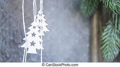 Two small white Christmas trees hanging on the background of a gray wall