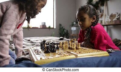 Two smart little girls playing chess on bed - Intellegent...