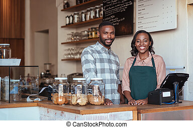 Two smiling African entrepreneurs standing behind their cafe counter