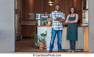 Two smiling African entrepreneurs standing in front of their...