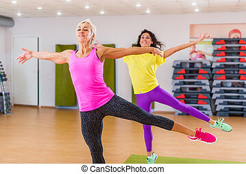 two smiling athletic women doing aerobic dancing exercises